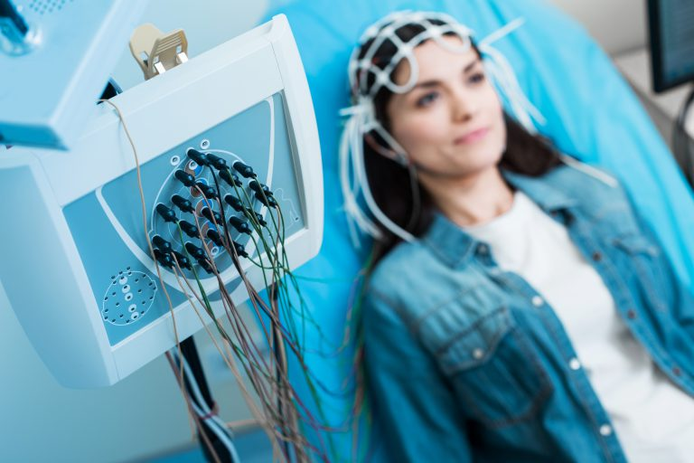 Top-notch equipment. The focus being on a modern electroencephalograph being connected to the head of a charming young woman